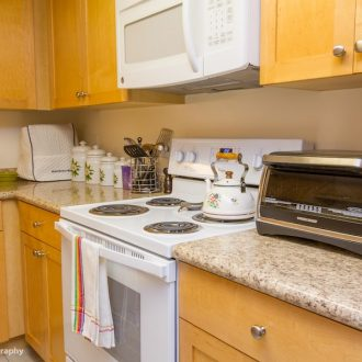 An electric cooking range and microwave in the kitchen of the Dogwood floor plan.