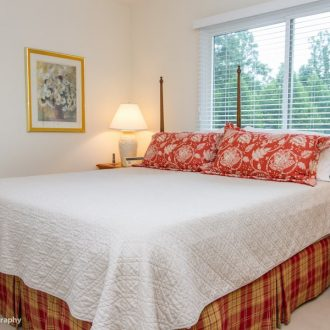 A large king-size bed in a brightly lit bedroom of the Dogwood floor plan.
