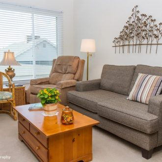 A sofa and a chair in front of a coffee table in the Dogwood floor plan.