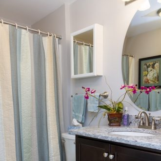 A bathroom with a shower, toilet, and mirror in the Laurel floor plan at Ardenwoods.