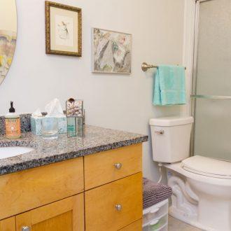 A bathroom with granite countertops in the Azalea floor plan at Ardenwoods.
