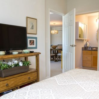 The bedroom with a television in the Azalea floor plan at Ardenwoods.