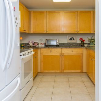 The kitchen of the Azalea floor plan with a fridge and granite countertops.