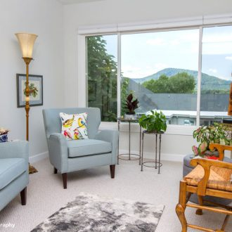 A furnished living room in the Azalea floor plan with a beautiful view of the mountains.