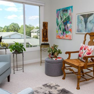 The living room in the Azalea floor plan with chairs and art.