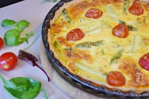 A beautiful quiche with tomato and basil.