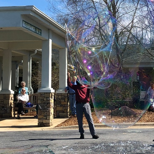 A bubble artist making large bubbles for the residents at Ardenwoods.
